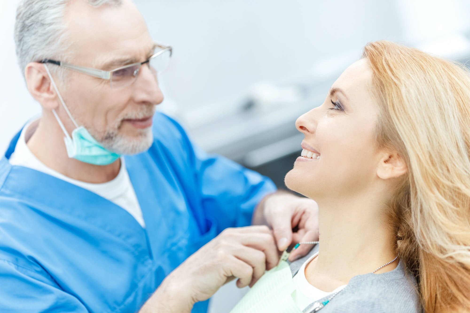 senior dentist in uniform talking with patient in dental clinic